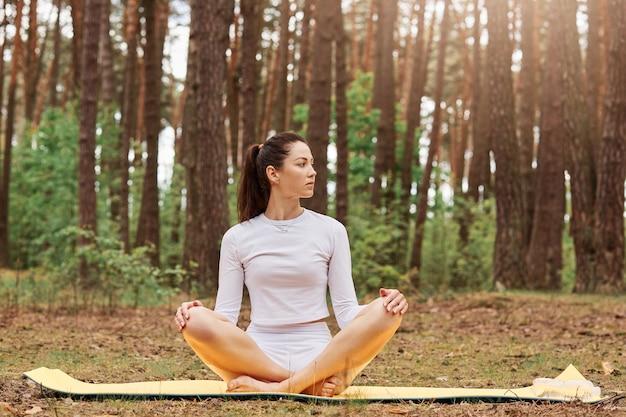 Giovane donna attraente con i capelli scuri che guarda lontano mentre medita all'aria aperta, ragazza seduta nella posa del loto con le gambe incrociate su mat