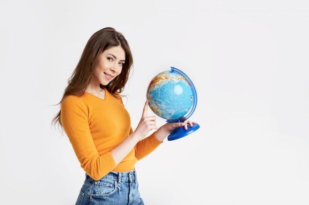 Una giovane ragazza attraente sceglie un posto per riposare su un grande globo. vacanze, viaggi. ritratto su uno sfondo chiaro con spazio per il testo