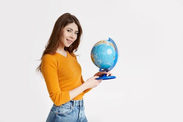 Una giovane ragazza attraente sceglie un posto per riposare su un grande globo