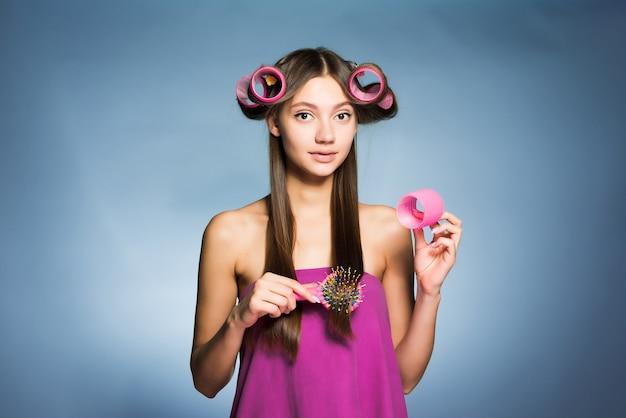 La giovane ragazza attraente fa un'acconciatura alla moda con i grandi bigodini e pettini