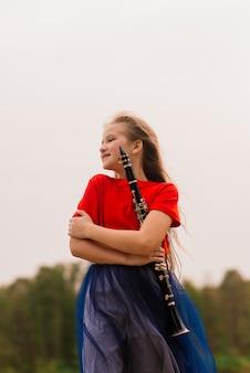 Giovane ragazza attraente che gioca clarinetto, ebano nel parco di caduta