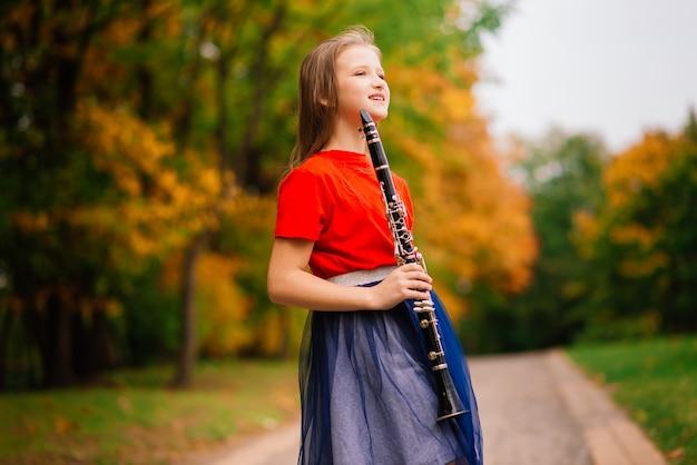 Giovane ragazza attraente che suona il clarinetto, ebano nel parco autunnale