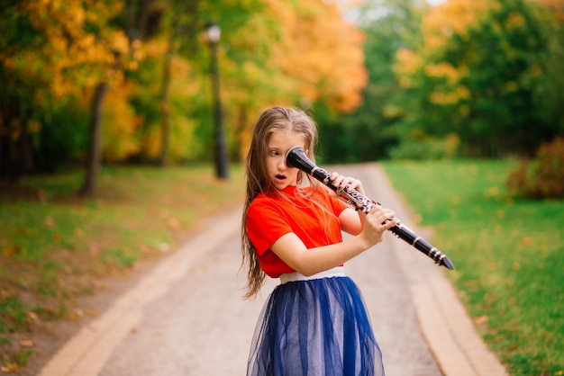 Giovane ragazza attraente che gioca clarinetto