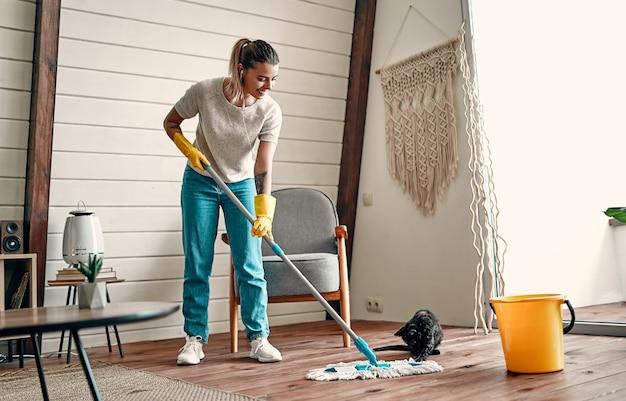 Una giovane ragazza attraente in guanti di gomma e cuffie ascolta musica e pulisce il pavimento di legno nella sua stanza. il gatto gioca divertente con una scopa.
