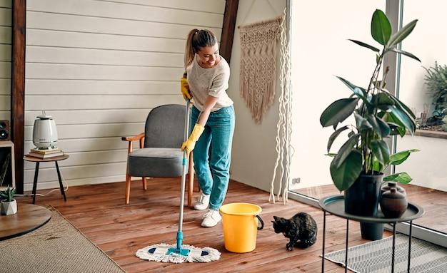 Una giovane ragazza attraente in guanti di gomma e cuffie ascolta musica e pulisce il pavimento di legno nella sua stanza. pulizia generale della casa.