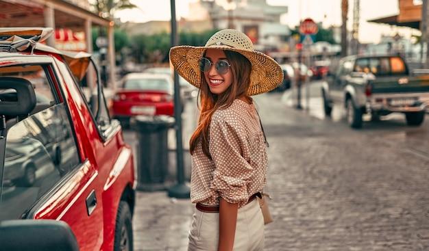Giovane turista attraente ragazza in una camicetta, un cappello di paglia e occhiali da sole, che cammina per le strade della città da una macchina rossa. il concetto di turismo, viaggi.