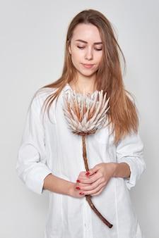 Giovane ragazza attraente che indossa una camicia bianca che tiene un fiore.