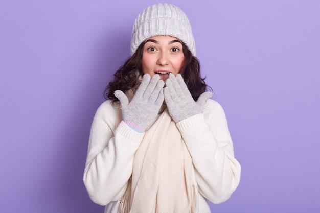 Giovane ragazza attraente che indossa un maglione bianco, berretto caldo, sciarpa e guanti, con trucco leggero, coprendosi la bocca con le mani