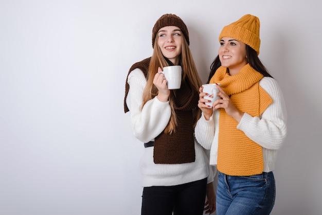 Giovani ragazze attraenti sopra backgris grigio che tiene tazze bianche