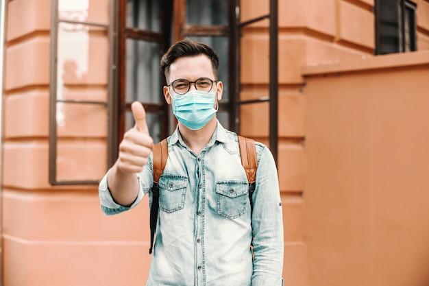 Giovani attraenti hipster con maschera sul viso in piedi all'aperto e mostrando i pollici in su. epidemia di covid19.