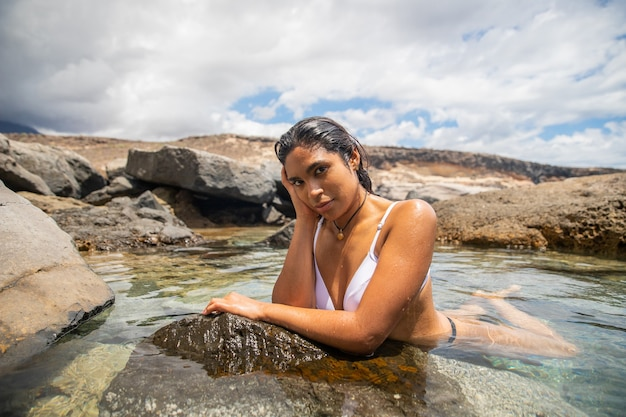 Giovane ragazza latina attraente che posa in una piscina naturale con acqua cristallina è estate e c'è un tempo soleggiato