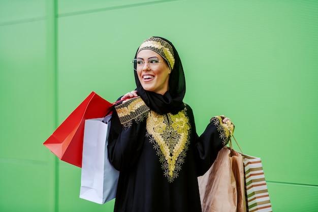 Giovane donna araba che ride attraente nell'usura tradizionale che cammina all'aperto con le borse della spesa nelle mani. è soddisfatta del suo acquisto.