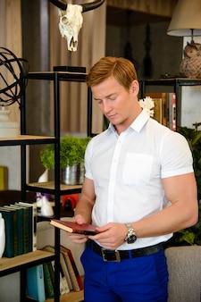 Giovane culturista maschio attraente che legge il libro.