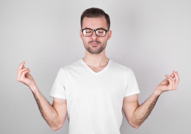 Il giovane uomo attraente medita nella posizione del loto su grigio.