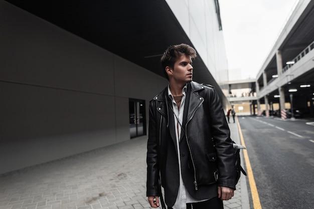 Modello di giovane uomo attraente in una giacca di pelle nera alla moda oversize in una camicia in pantaloni con uno zaino alla moda si alza e guarda da parte su una strada della città. il ragazzo alla moda hipster cammina.