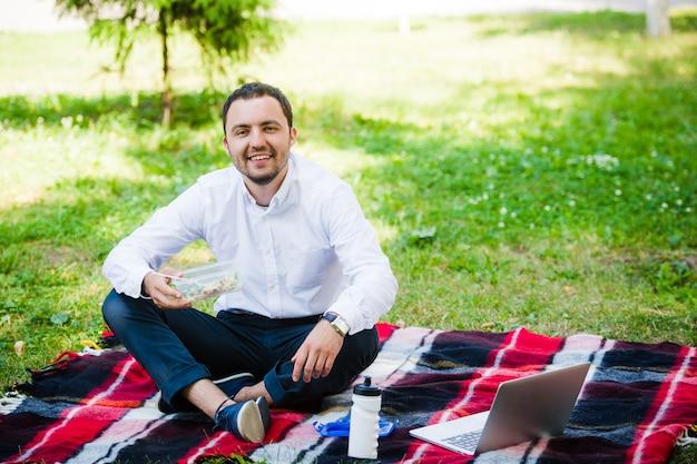 L'uomo giovane e attraente si rilassa nel parco all'ora di pranzo