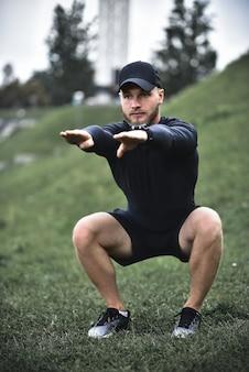 Giovane uomo attraente accovacciato all'aperto nel parco con le mani tese.