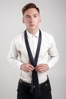 Giovane uomo attraente in camicia bianca in posa. il ragazzo si raddrizza la cravatta