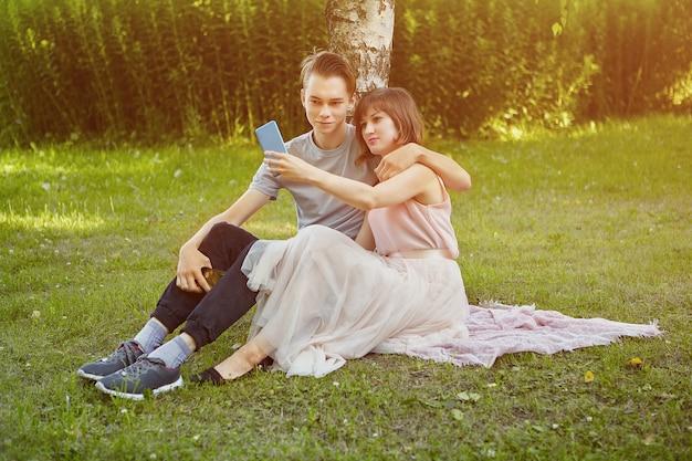 Giovane uomo e donna attraenti sta prendendo selfie tramite smartphone mentre era seduto sull'erba nel parco pubblico.