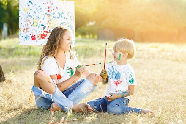 Giovane madre attraente divertirsi con i suoi figli al parco. divertimento allegro della famiglia all'aperto. la mamma gioca con i suoi figli.