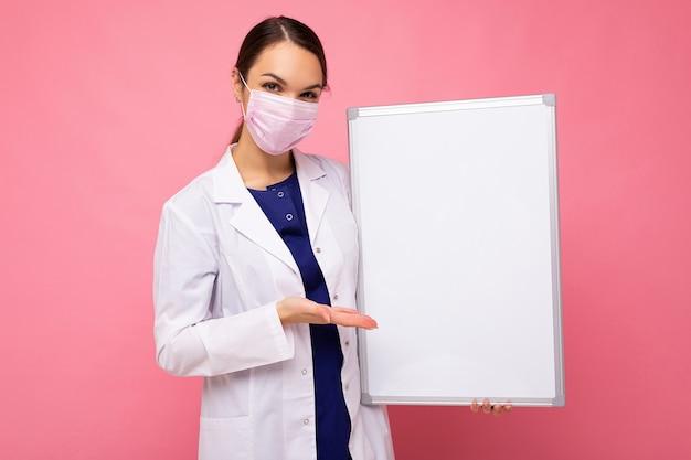 Giovane infermiera attraente in maschera protettiva che tiene una lavagna magnetica vuota isolata su sfondo rosa.