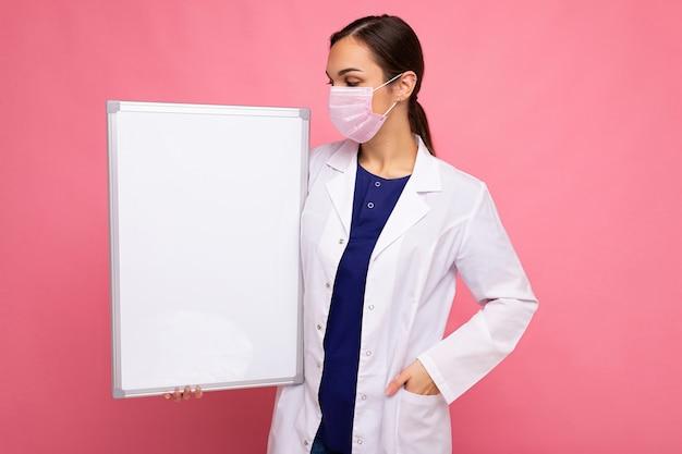 Giovane infermiera attraente con maschera protettiva che tiene una lavagna magnetica vuota isolata su sfondo rosa