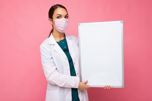 Giovane infermiera attraente con maschera protettiva che tiene una lavagna magnetica vuota