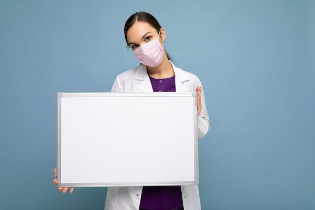 Giovane infermiera attraente in maschera protettiva e camice medico bianco che tiene un bordo magnetico vuoto isolato su priorità bassa blu.