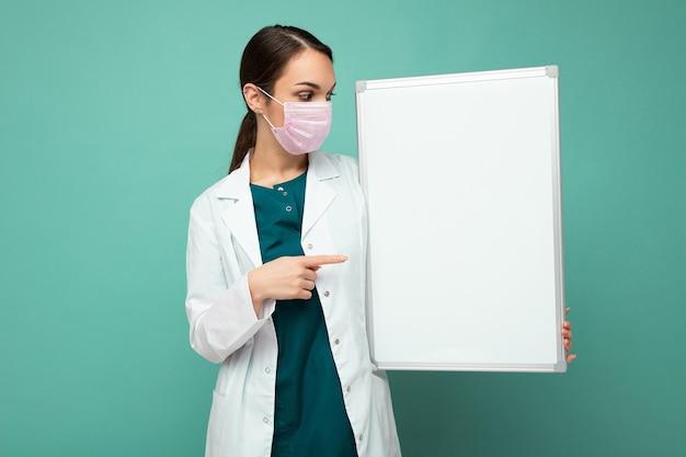 Giovane infermiera attraente in maschera protettiva e camice bianco medico che tiene una lavagna magnetica vuota isolata su sfondo blu Foto Premium