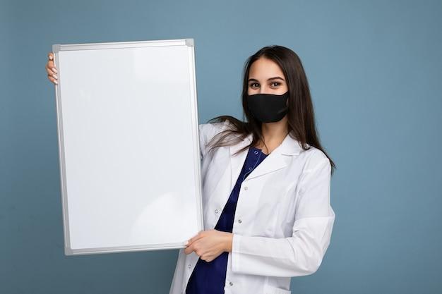 Giovane infermiera attraente in maschera protettiva e camice bianco medico che tiene una lavagna magnetica vuota isolata su sfondo blu