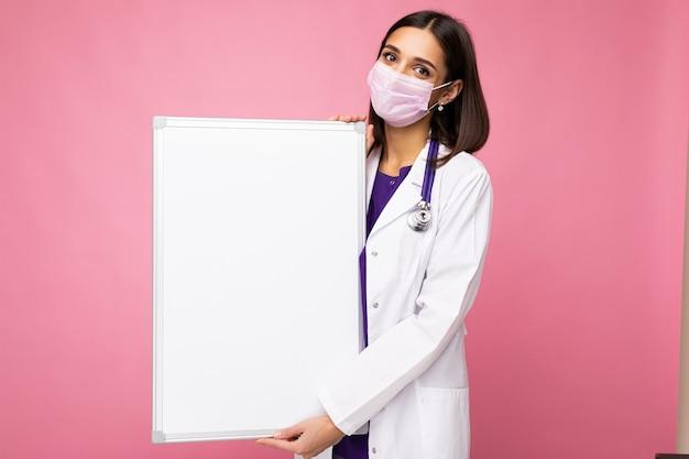 Giovane infermiera attraente in maschera protettiva e camice bianco medico che tiene una lavagna magnetica vuota isolata su sfondo rosa