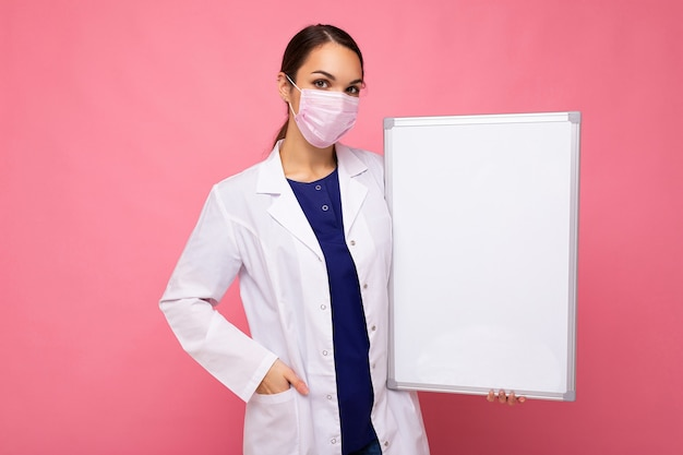 Giovane infermiera attraente in maschera protettiva