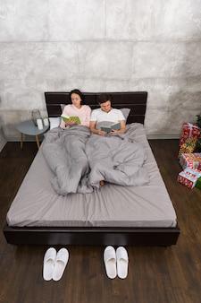 Giovane coppia attraente che legge libri mentre è sdraiata a letto e indossa un pigiama in camera da letto, vicino a pantofole bianche e regali