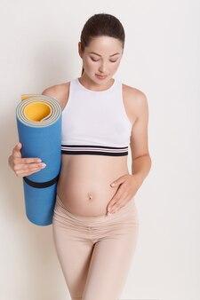 Giovane femmina incinta attraente che tocca la sua pancia mentre tenendo la stuoia di yoga in mani