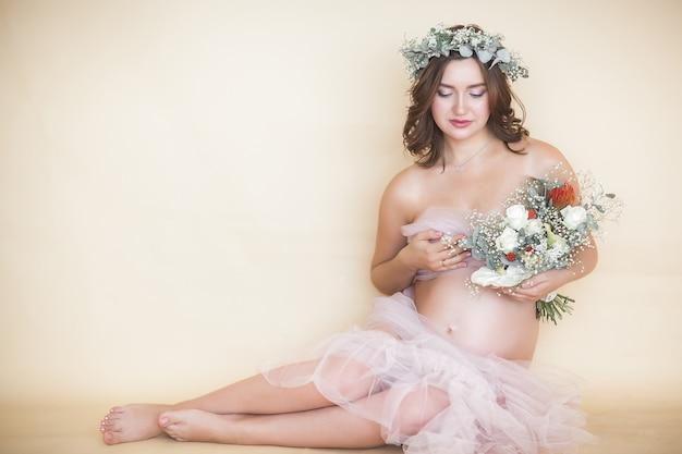 Giovane donna incinta attraente a casa. close up ritratto di attesa femmina.