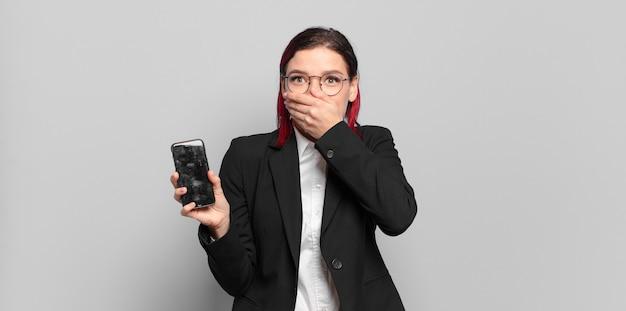 Giovane donna attraente con i capelli rossi che copre la bocca con le mani con un'espressione scioccata e sorpresa, mantenendo un segreto o dicendo oops. concetto di affari