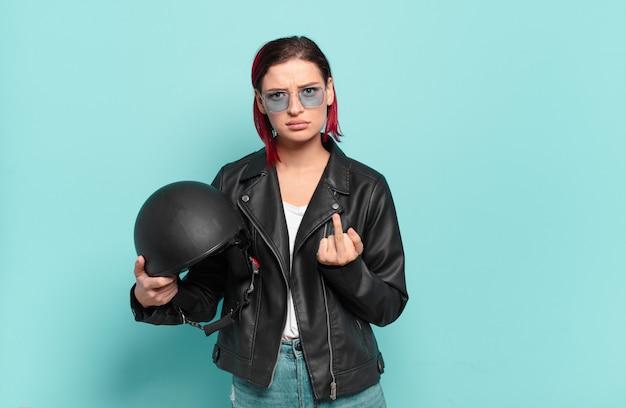 Giovane donna attraente con i capelli rossi che si sente arrabbiata, infastidita, ribelle e aggressiva, lancia il dito medio, reagisce.