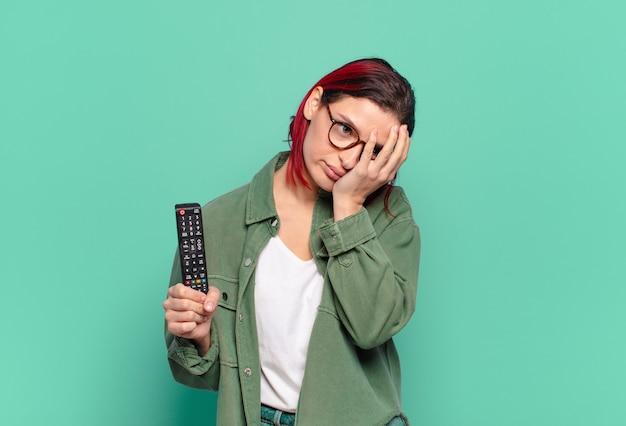 Giovane donna attraente dai capelli rossi che si sente annoiata, frustrata e assonnata dopo un compito noioso, noioso e noioso, tenendo il viso con la mano e tenendo in mano un telecomando della tv