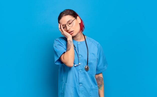 Giovane donna attraente con i capelli rossi che si sente annoiata, frustrata e assonnata dopo un compito noioso, noioso e noioso, tenendo il viso con la mano. concetto di infermiera ospedaliera