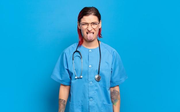 Giovane donna attraente dai capelli rossi che si sente disgustata e irritata, tira fuori la lingua, non ama qualcosa di brutto e schifoso. concetto di infermiera ospedaliera