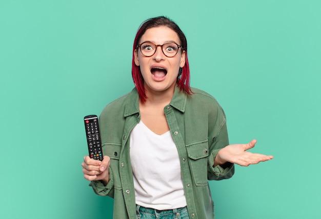 Giovane donna attraente dai capelli rossi che si sente estremamente scioccata e sorpresa
