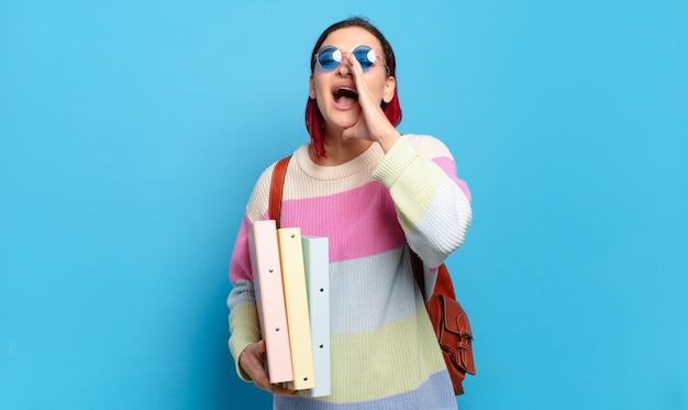 Giovane donna attraente con i capelli rossi che si sente felice, eccitata e positiva, dando un grande grido con le mani vicino alla bocca, chiamando. concetto di studente universitario