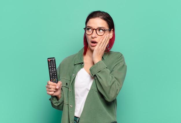 Giovane donna attraente dai capelli rossi che si sente felice, eccitata e sorpresa, guardando di lato con entrambe le mani sul viso e tenendo in mano un telecomando della tv