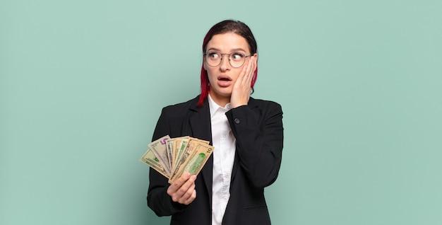 Giovane donna attraente dai capelli rossi sentirsi felice, eccitata e sorpresa, guardando di lato con entrambe le mani sul viso. concetto di denaro