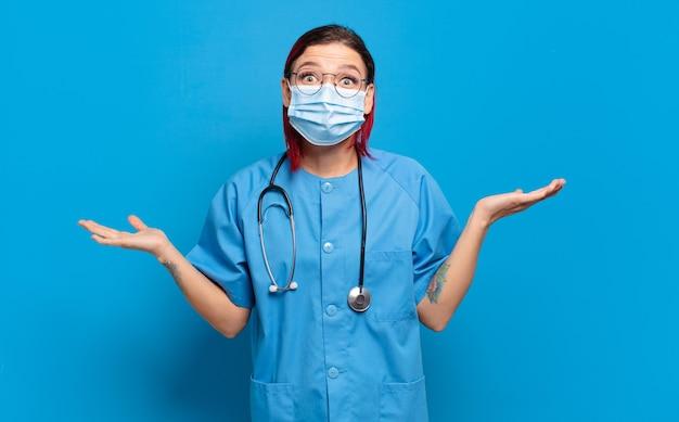 Giovane donna dai capelli rossi attraente che si sente felice, eccitata, sorpresa o scioccata, sorridente e stupita da qualcosa di incredibile. concetto di infermiera ospedaliera