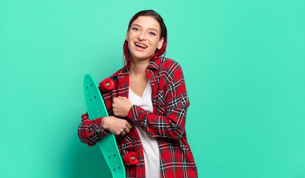 Giovane donna attraente dai capelli rossi che si sente felice, positiva e di successo, motivata quando affronta una sfida o celebra i buoni risultati e tiene in mano uno skateboard