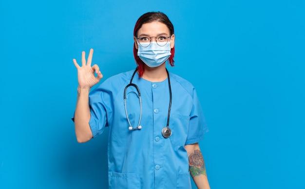 Giovane donna attraente dai capelli rossi sentirsi felice, rilassata e soddisfatta, mostrando approvazione con un gesto ok, sorridente. concetto di infermiera ospedaliera