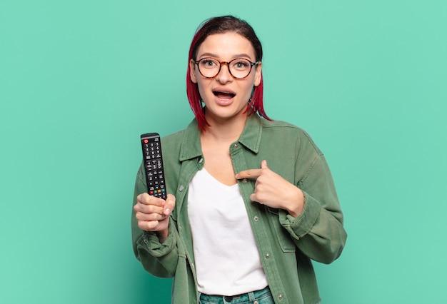 Giovane donna attraente dai capelli rossi che si sente felice, sorpresa e orgogliosa, indicando se stessa con un'eccitazione