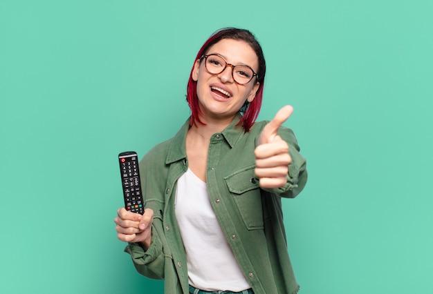 Giovane donna attraente dai capelli rossi che si sente orgogliosa, spensierata, sicura di sé e felice, sorride positivamente con il pollice in alto e tiene in mano un telecomando della tv
