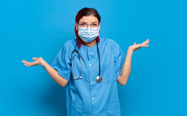 Giovane donna attraente con i capelli rossi che si sente perplessa e confusa, dubita, appesantisce o sceglie diverse opzioni con un'espressione divertente concetto di infermiera ospedaliera